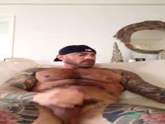 tattooed man wanking
